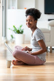 Afrikaanse Amerikaanse vrouw die laptop in haar woonkamer met behulp van - Zwarte Stock Afbeeldingen