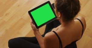 Afrikaanse Amerikaanse vrouw het letten op video's op tablet Stock Foto