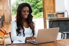 Afrikaanse Amerikaanse vrouw met lang haar die bij computer werken stock afbeelding