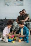Afrikaanse Amerikaanse vrouwelijke en mannelijke militairen die hun kinderen bekijken stock afbeelding