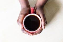 Afrikaanse Amerikaanse Vrouwelijke handen die rode kop van koffieespresso of cappuccino houden op counter-top van de granietkeuke stock foto