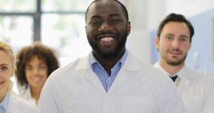 Afrikaanse Amerikaanse Wetenschapper Man Happy Smiling over het Laboratorium van Team Of Researchers In Modern van het Mengelings stock footage