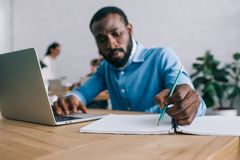 Afrikaanse Amerikaanse zakenman die in handboek schrijven en laptop met behulp van bij lijst en collega's stock afbeeldingen