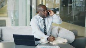 Afrikaanse Amerikaanse zakenman die op smartphone spreken en bedrijfsinformatie in zijn blocnotezitting binnen neerschrijven stock videobeelden