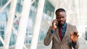 Afrikaanse Amerikaanse zakenman die op straat dichtbij bureaucentrum lopen en op mobiele telefoon spreken Zaken, mensen