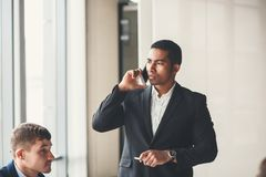 Afrikaanse Amerikaanse zakenman die slimme of telefoon met behulp van die met de elektronische post versturen spreken stock foto