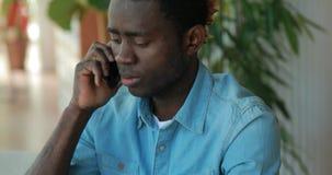 Afrikaanse Amerikaanse zakenman die telefonisch spreken terwijl het gebruiken van laptop computer in koffie stock footage