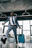 Afrikaanse Amerikaanse zakenman die voor vlucht bij luchthaven lopen stock fotografie