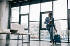 Afrikaanse Amerikaanse zakenman die zich omhoog voor vlucht bij luchthaven haasten stock foto's