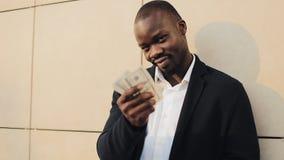 Afrikaanse Amerikaanse zakenman in een kostuum tellend geld en het tonen van geld in de camera Hij die zijn succesvol vieren stock video