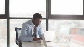 Afrikaanse Amerikaanse zakenman in een pak die aan laptop werken stock footage