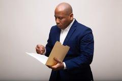 Afrikaanse Amerikaanse Zakenman Looks Through Folder royalty-vrije stock fotografie