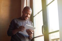 Afrikaanse Amerikaanse zwarte mens die elektronische tablet thuis gebruiken royalty-vrije stock fotografie