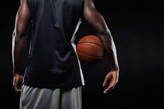 Afrikaanse basketbalspeler met een bal in zijn wapen Royalty-vrije Stock Foto