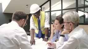 Afrikaanse bouwer die huisblauwdruk voorstellen aan collega's op briefing in vergaderzaal stock footage