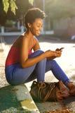 Afrikaanse damevrouw die mobiele telefoon met behulp van Royalty-vrije Stock Foto
