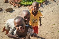 Afrikaanse dorpskinderen die dichtbij de meerkust spelen in de voorstad van Fort Portal stock fotografie