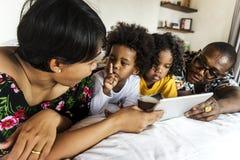 Afrikaanse familie op bed die een tablet gebruiken stock afbeelding