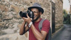 Afrikaanse gelukkige toerist die foto op zijn dslrcamera nemen Jonge mens die in Europa reizen stock afbeeldingen