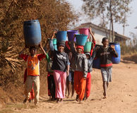 Afrikaanse jonge geitjes die water dragen Stock Foto's