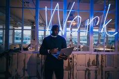Afrikaanse jonge mens die zich in bureau bevinden die laptop met behulp van stock afbeelding