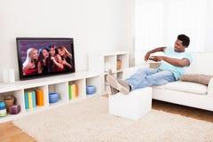 Afrikaanse jonge mens het letten op televisie royalty-vrije stock foto