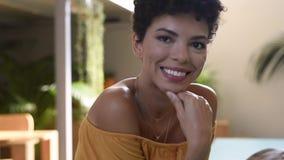 Afrikaanse jonge vrouw die en camera glimlachen bekijken stock video