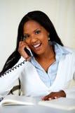 Afrikaanse jonge vrouw die op telefoon spreekt Stock Afbeeldingen