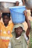Afrikaanse jongens die dozen met voedsel op hoofden dragen Stock Fotografie