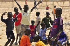 Afrikaanse jongens die voetbal op het strand spelen Stock Foto