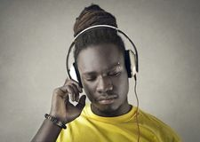 Afrikaanse kerel die aan muziek met hoofdtelefoons luisteren stock foto