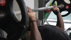 Afrikaanse kerel die barbell bankpers in gymnastiek doen de Afro-Amerikaanse Jonge mens ligt op bank stock videobeelden