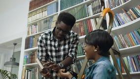 Afrikaanse kerel die zich op ladder bevinden en boeken geven aan Afrikaans meisje in universitaire bibliotheek stock videobeelden