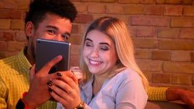 Afrikaanse kerel en Kaukasische meisjeszitting op bank die thuis grappige selfie-foto's op tablet spreken die blij en gelukkig zi stock videobeelden