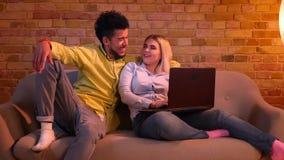 Afrikaanse kerel en Kaukasische meisjeszitting op bank met laptop en vreugdevol thuis het spreken met elkaar stock video
