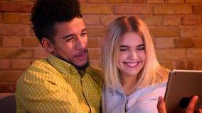 Afrikaanse kerel en Kaukasische meisjeszitting op bank sprekende selfie-foto's op tablet die gelukkig thuis zijn stock videobeelden