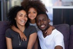 Afrikaanse kinddochter die jonge houdende van zwarte ouders, portret omhelzen royalty-vrije stock fotografie