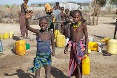 Afrikaanse kinderen en watervoorziening Stock Foto's