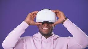 Afrikaanse knappe mens die sporten dragen die hoodie een VR-hoofdtelefoon van zijn hoofd dragen stock video