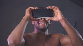 Afrikaanse knappe mens die sporten dragen die hoodie een VR-hoofdtelefoon van zijn hoofd dragen stock footage