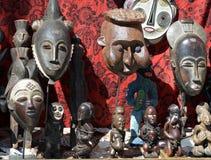 Afrikaanse maskers en standbeelden bij een vlooienmarkt Stock Afbeeldingen