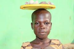 Afrikaanse meisjes carying stenen op haar hoofd Stock Fotografie