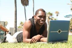 Afrikaanse Mens Amercian die aan Laptop werkt stock foto's