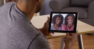 Afrikaanse mens die aan verwanten met tablet spreken Royalty-vrije Stock Afbeelding