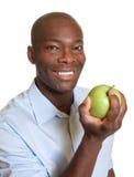 Afrikaanse mens die een appel eten stock foto's