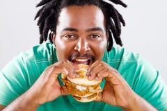 Afrikaanse mens die hamburger eet Royalty-vrije Stock Fotografie