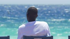 Afrikaanse mens die in oortelefoons aan muziek bij kust luisteren, die aard van mening genieten stock videobeelden