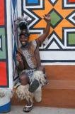 Afrikaanse mens die in traditionele kleding aan de camera in Lesedi glimlachen Royalty-vrije Stock Afbeelding