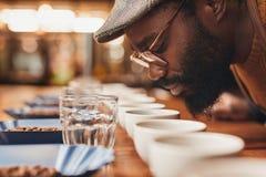 Afrikaanse mens die van het aroma van verse koffie genieten bij het proeven royalty-vrije stock foto