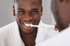 Afrikaanse Mens die Zijn Tanden in Front Of Mirror schoonmaken royalty-vrije stock foto